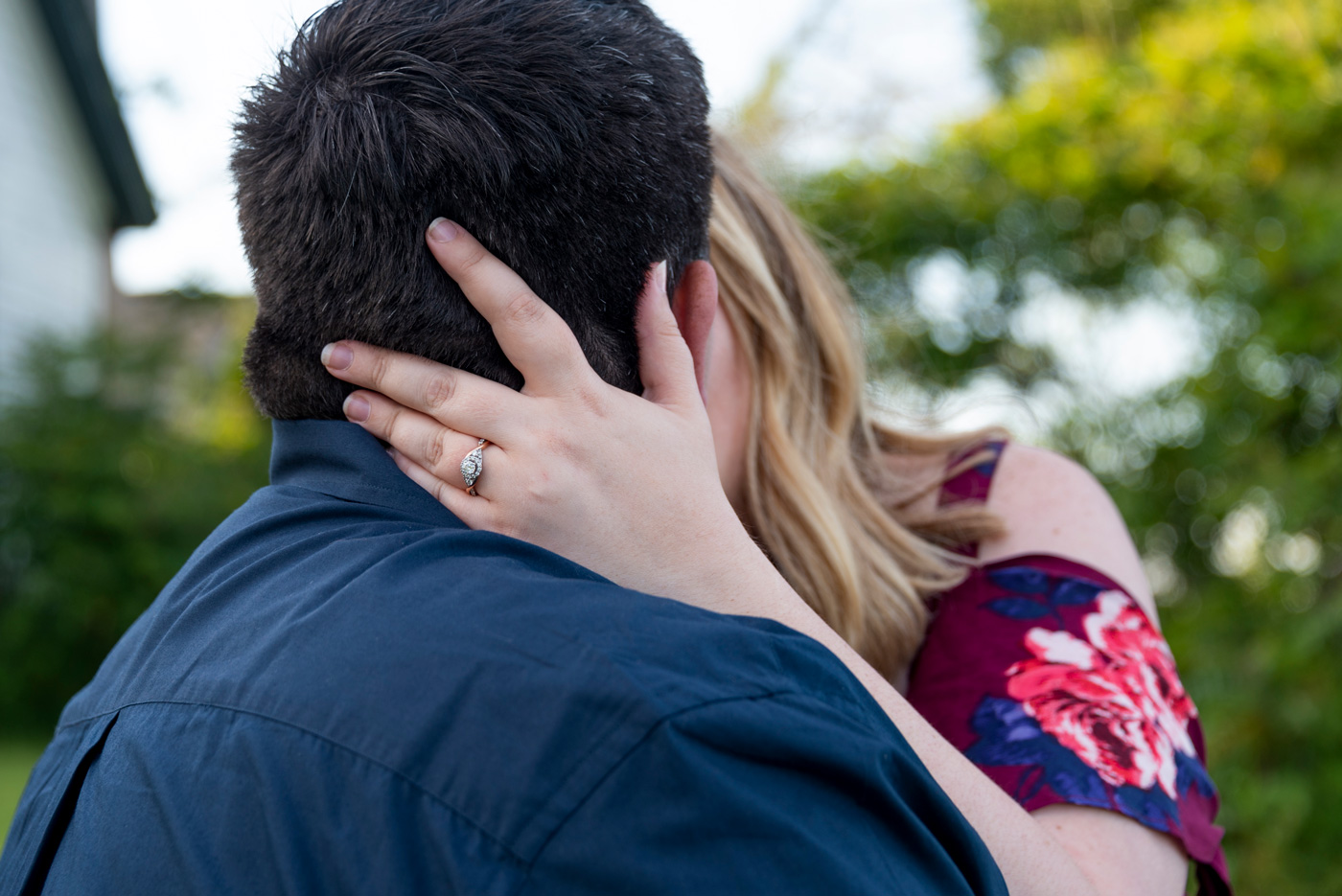 engagement ring shot while kissing